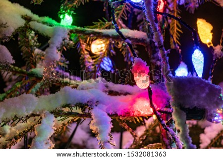 Very shiny Christmas decorations outside, night, Northern countries, Led lamps usage to save energy for green environment, snow corn, fir tree needles illuminated by lamps that on the Christmas tree