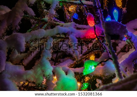 Very shiny Christmas decorations outside, night, Northern countries, Led lamps usage to save energy for green environment, snow corn, fir tree needles illuminated by lamps that on the Christmas tree #1532081366