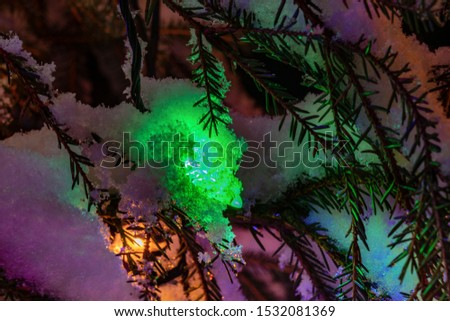 Very shiny Christmas decorations outside, night, Northern countries, Led lamps usage to save energy for green environment, snow corn, fir tree needles illuminated by lamps that on the Christmas tree #1532081369