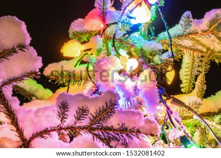 Very shiny Christmas decorations outside, night, Northern countries, Led lamps usage to save energy for green environment, snow corn, fir tree needles illuminated by lamps that on the Christmas tree #1532081402