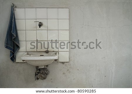 very simple old washbasin over a  white grunge wall