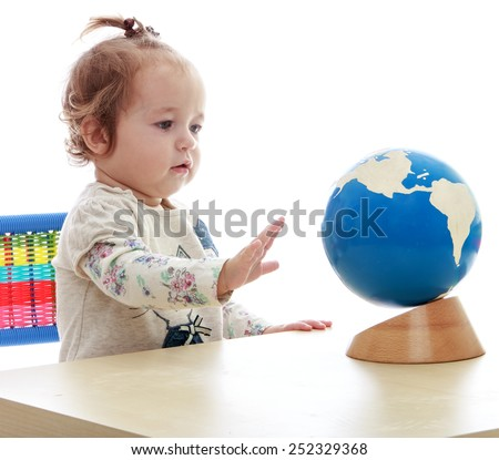 very small but serious little girl spinning globe hand.Isolated on white background, Lotus Children\'s Center.