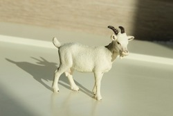 very small toy plastic kid, goatling with shadow on a wooden table
