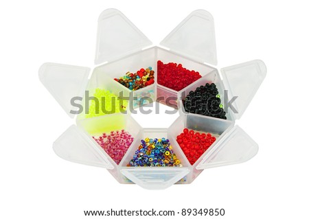 very special crown shape plastic box with multicolored bright glass beads isolated over white