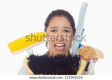 Very stressed young woman with cleaning tools
