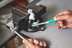 Very thrifty person squeezes the toothpaste from the tube onto a twisted brush clamped in the bench screw