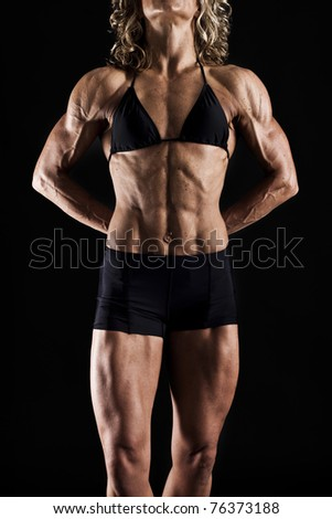 Very toned female body builder - stock photo