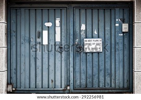 Very weathered and abused metal blue double doors with a sign, \