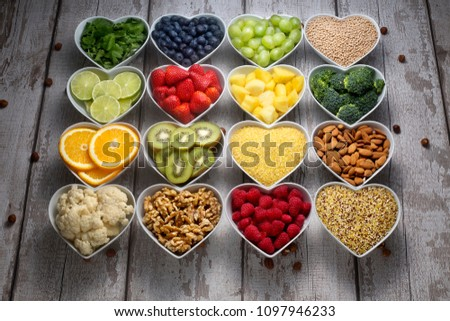 very well displayed variety of fruits and nuts filled in heart shape bowls. #1097946233