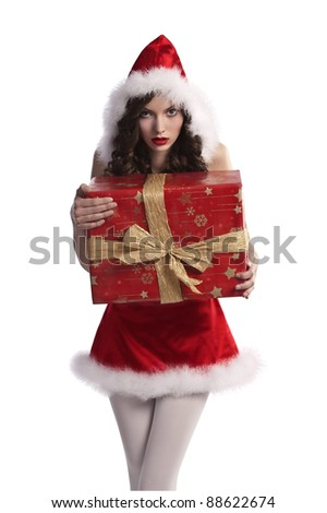 very young beautiful girl wearing a santa claus costum with fur holding a huge gift box in her hands