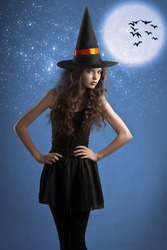 very young girl dressed as halloween witch posing under stars and moon wearing a huge witch hat