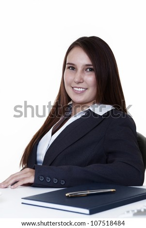 very young looking woman with a big smile sitting at her desk