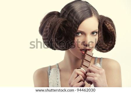 very young pretty girl with creative hairstyle eating a tablet of chocolate wearing a old style dress