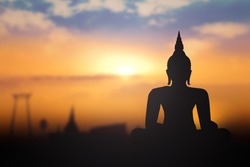 Vesak day concept: Silhouette Buddha with blurred travel tourist attraction in Thailand - Asia on golden temple sunset background