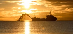 Vessel engaged in dredging at sunset time. Hopper dredger working at sea. Ship excavating material from a water environment. Beautiful sunset.