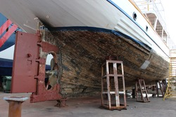 Vessel in the shipyard dry dock. Hull maintenance and shipyard ground works.