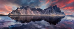 Vestrahorn mountaine on Stokksnes cape in Iceland during sunset with reflections. Amazing Iceland nature seascape. popular tourist attraction. Best famouse travel locations. Scenic Image of Iceland