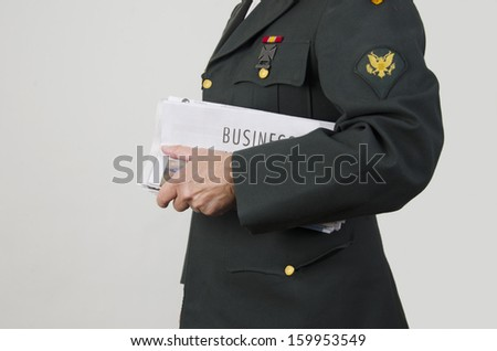 Veteran holding newspaper with business section/Veteran Looking for Work/Veteran in an army uniform holding business pages