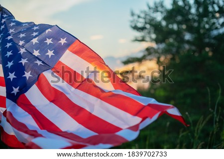 Veterans Day Flag Of The United States Of America. American flag flying on the background of the setting sun in nature.