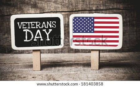 Veterans Day holiday sign written on a chalkboard with American flag on wooden background