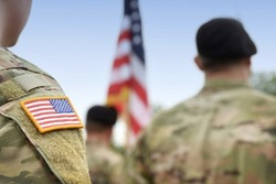 Veterans Day. US soldiers. US army. USA patch flag on the US military uniform. Soldiers on the parade ground from the back.