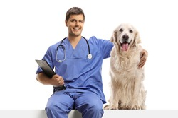 Veterinarian doc in a blue uniform sitting on a white panel and hugging a retriever dog isolated on white background