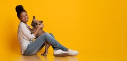 Veterinary Clinic Advertisement Concept. Happy Afro Woman Dog Owner With Her Cute French Bulldog Puppy, Sitting On Floor Over Yellow Background