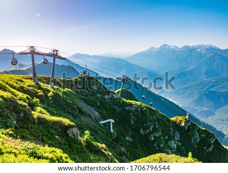Vew in the summer sunset to the ski resort Rosa Khutor from the top of the Aibga range. Beautiful sunset in mountains with the cable car. Krasnaya Polyana, Sochi, Caucasus, Russia