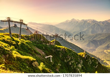 Vew in the summer sunset to the ski resort Rosa Khutor from the top of the Aibga range. Beautiful orange sunset in mountains with the cable car. Krasnaya Polyana, Sochi, Caucasus, Russia