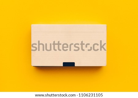 VHS video cassette on yellow background, flat lay top view minimalistic composition for retro technology themes
