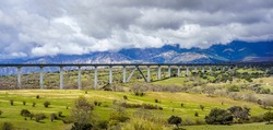 Viaduct or bridge where the high-speed train ave passes, in a green landscape with dark storm clouds. Madrid.