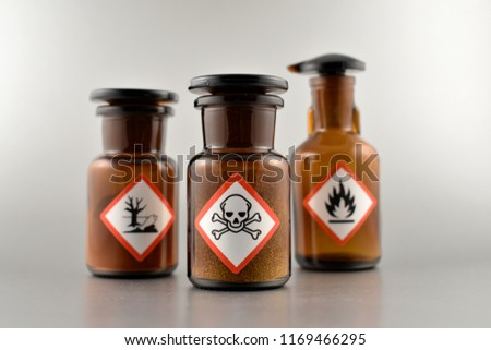 Vial with warning pictogram stock images. Laboratory accessories. Vials on a silver background. Brown glass containers. Brown chemical glass #1169466295