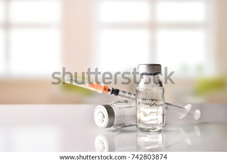 Vials with medication and syringe on white methacrylate table with window background. Horizontal composition. Front view.