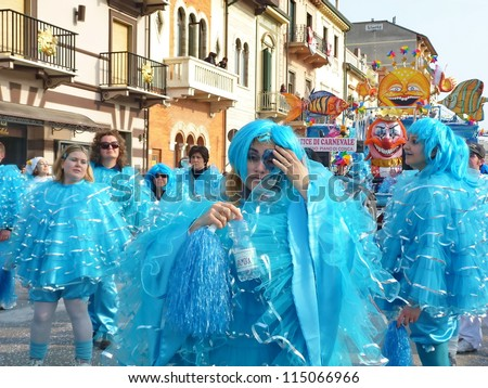 VIAREGGIO, ITALY - MARCH 4:Group masked at the parades on the promenade during the famous annual Italian Carnival of Viareggio on march 4, 2012 in Viareggio, Italy