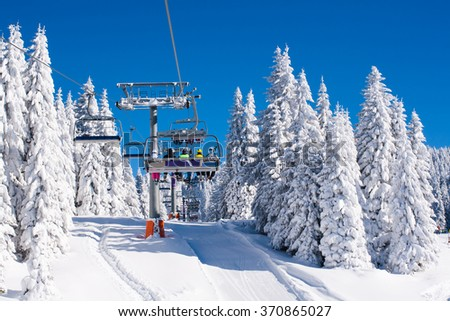Vibrant active people winter image with skiers sitting on the ski lift, ski slope among white snow pine trees, blue sky #370865027