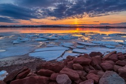 Vibrant and serene winter landscape with a single frozen ice sheet floating on a lake during a late sunset in Charlottetown, Prince Edward Island, Canada.