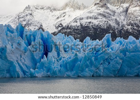 Vibrant blue icebergs in front of snowy mountains taken at Grey Glacier in Torres del Paine National Park, Patagonia.