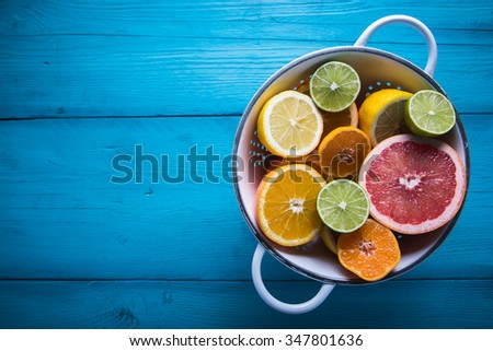 Vibrant citrus half cut fruits on wooden table #347801636