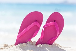 Vibrant color flip flops in white sand on sea background