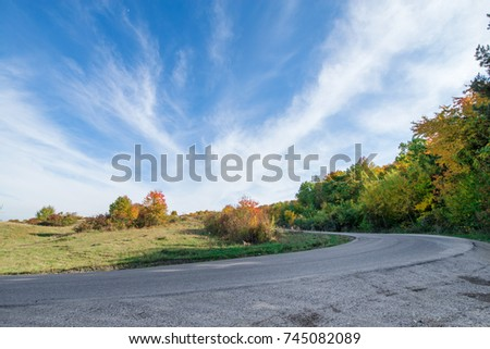 Vibrant colored trees at mountainside next to a serpentine road in mountains in late autumn. Empty highway. Beautiful, colorful autumn background with blue sky  #745082089