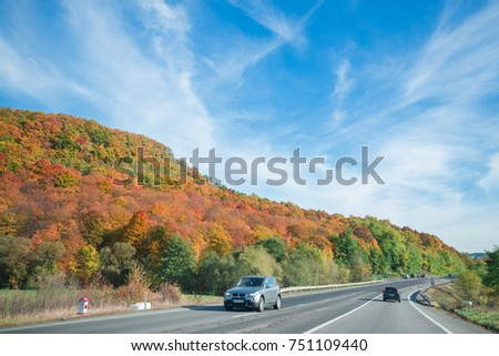 Vibrant colored trees on at mountainside next to a busy highway in late autumn. Beautiful, colorful autumn background #751109440