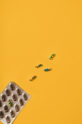 Vibrant colorful flat lay of medicine pill capsules filled with sugar candy sprinkles on yellow background. Creative concept of overdose medicine usage and addiction to food supplement.