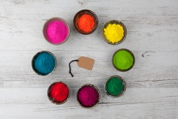 Vibrant colorful Holi powder in cups arranged in circle with gift tag in the middle. Top view