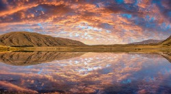 Vibrant coloured cloudscape at Ashburton lakes district with a stunning sunset reflection on the water surface