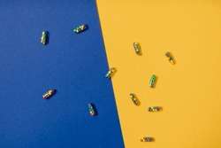Vibrant colourful flat lay of medicine pill capsules filled with sugar candy sprinkles on yellow and blue background. Creative concept of overdose medicine usage and addiction to food supplement.