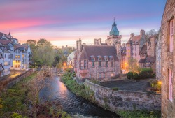 Vibrant, colourful sunset or sunrise sky over the historic architecture of Dean Village along the Water of Leith in Edinburgh, Scotland.