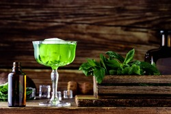 Vibrant green cocktail with fresh mint leaves with wooden background
