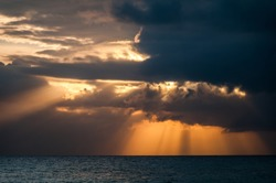 Vibrant orange sunrays shine through the clouds above the calm caribbean sea during sunset.