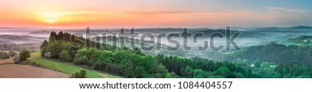 Vibrant panoramic sunrise over countryside hills in Poland. Spring mist and green fields.