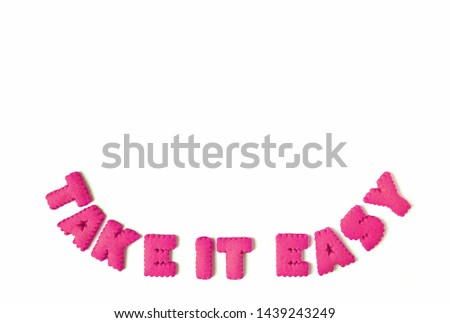 Vibrant pink alphabet shaped cookies spelling the word TAKE IT EASY on white background #1439243249